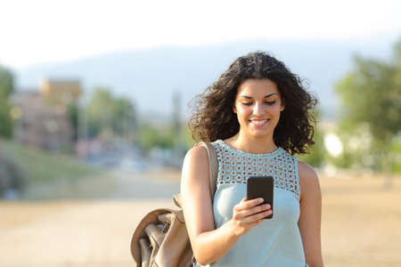 Foto de Front view of a happy girl walking and using a smart phone in a town - Imagen libre de derechos