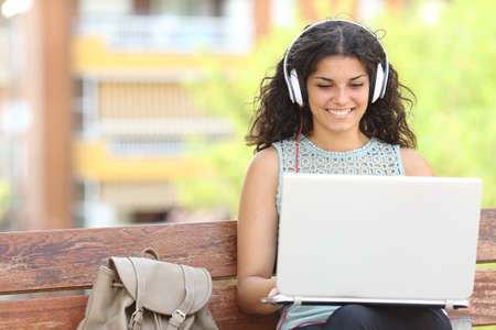 Foto de Freelancer working with a laptop and headphones sitting on a bench in a park - Imagen libre de derechos