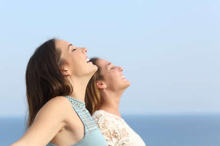 Photo for Two girls doing breath exercises inhaling fresh air on the beach - Royalty Free Image