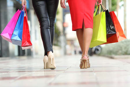 Photo pour Two fashion women legs walking with colorful shopping bags in the street of a city - image libre de droit
