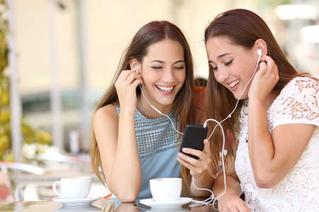 Photo pour Friends sharing and listening to music with earphones and smartphone in a coffee shop - image libre de droit