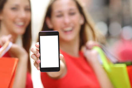 Photo pour Two joyful shoppers with shopping bags showing a blank smart phone screen in the street - image libre de droit