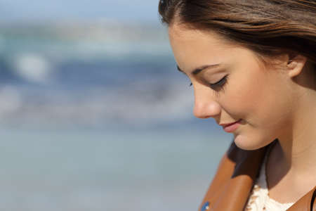 Foto de Close up portrait of a melancholic woman thinking on the beach with the sea in the background - Imagen libre de derechos
