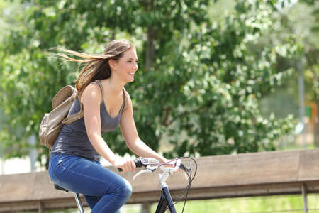 Photo pour Healthy and happy cyclist woman riding fast a bicycle in a park - image libre de droit