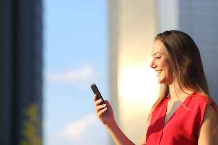 Foto de Entrepreneur business woman using a smart phone with office buildings in the background - Imagen libre de derechos