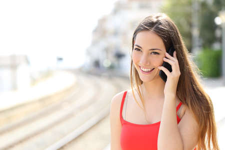 Foto de Lady talking on the mobile phone while is waiting in a train station in summer - Imagen libre de derechos