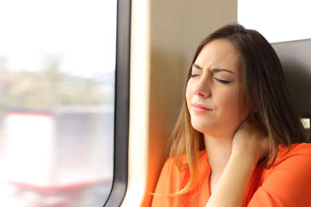 Photo pour Stressed woman with neck ache sitting in a train wagon complaints - image libre de droit