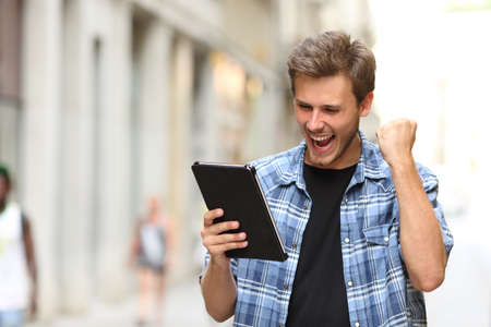 Photo pour Euphoric winner man screaming with a tablet in the street - image libre de droit