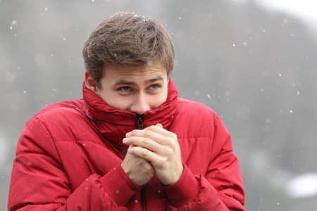 Foto de Man shivering in cold winter and rubbing hands while is snowing - Imagen libre de derechos
