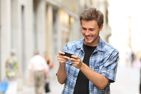 Photo pour Happy man playing game with a smart phone in the street - image libre de droit