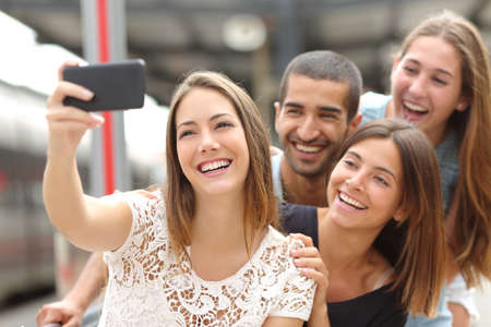 Foto de Group of four funny friends taking selfie with a smart phone in a train station in summer - Imagen libre de derechos