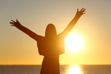 Photo pour Free happy woman raising arms watching the sun in the background at sunrise - image libre de droit