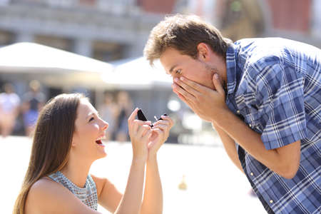 Photo for Proposal of a woman asking marry to a man in the middle of a street - Royalty Free Image