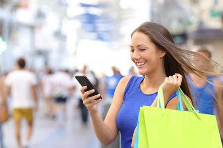 Foto de Shopper woman shopping with a smartphone in a commercial street - Imagen libre de derechos
