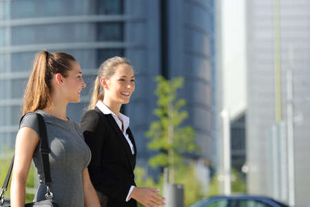Two happy businesswomen walking and talking in the street with office buildings in the background