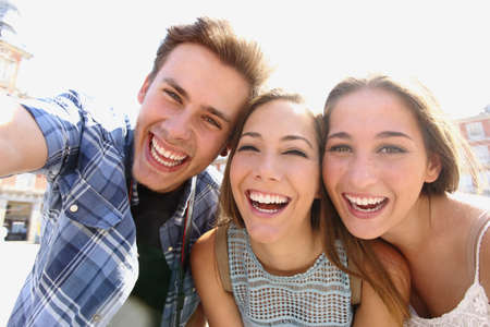 Foto de Group of happy teen friends laughing and taking a selfie in the street - Imagen libre de derechos
