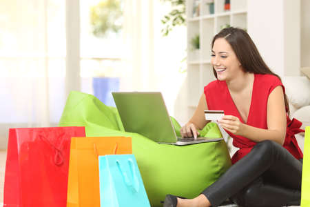 Photo pour Woman buying online at home with a credit card and multiple shopping bags beside - image libre de droit