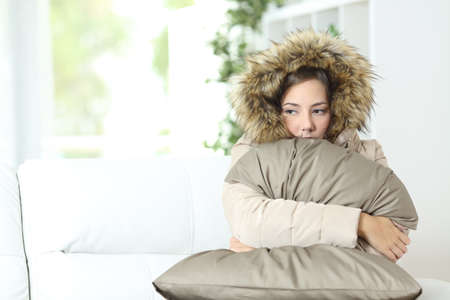 Photo pour Angry woman warmly clothed in a cold home sitting on a couch - image libre de droit