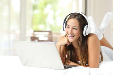 Foto de Girl with headphones listening to the music in a laptop on the bed at home - Imagen libre de derechos