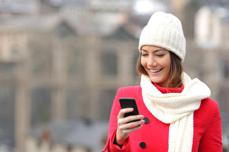 Photo for Girl texting in a mobile phone warmly clothed inthe street in winter - Royalty Free Image