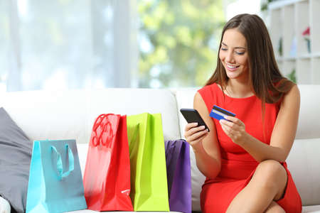 Photo pour Fashion girl buying online with smart phone and credit card with colorful shopping bags beside - image libre de droit