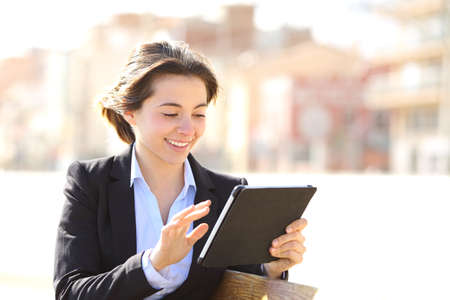 Photo pour Executive working browsing a tablet in a park sitting in a bench - image libre de droit