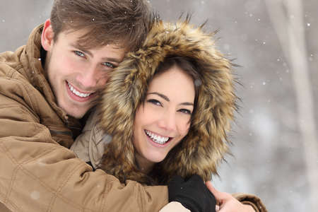 Photo pour Couple smiling with perfect teeth hugging and looking at camera in winter in a forest - image libre de droit