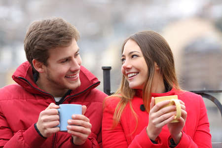 Photo for Couple talking relaxed sitting on a bench with coffee cups in winter - Royalty Free Image