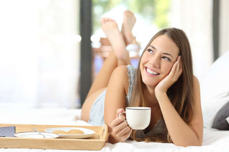 Foto de Happy girl having breakfast holding a coffee cup lying on the bed and looking sideways - Imagen libre de derechos