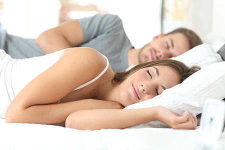 Photo pour Happy couple sleeping in a comfortable bed at home - image libre de droit