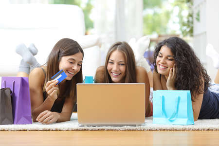 Photo pour Three friends shopping online with credit card and laptop lying on the floor at home - image libre de droit