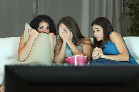 Photo for Girls watching a terror movie on tv sitting on a couch at home - Royalty Free Image