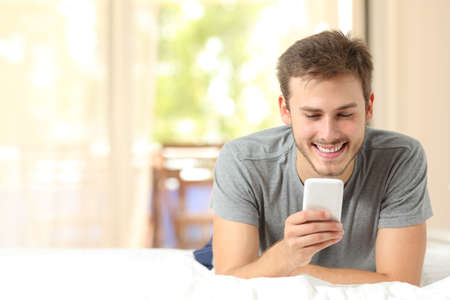 Photo pour Front view of a guy using a mobile phone in the bedroom at home - image libre de droit