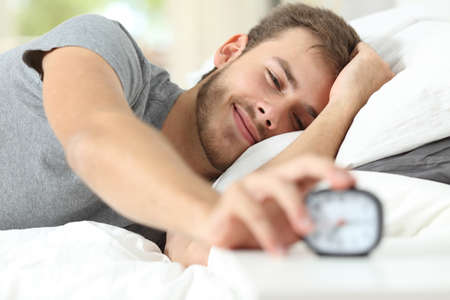 Photo for Happy wake up of a happy man lying on the bed and stopping alarm clock - Royalty Free Image