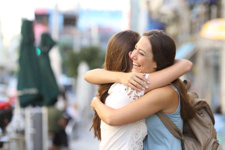 Photo pour Happy meeting of two friends hugging in the street - image libre de droit