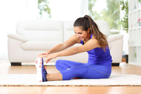 Photo for Fitness woman stretching legs sitting on the floor at home - Royalty Free Image