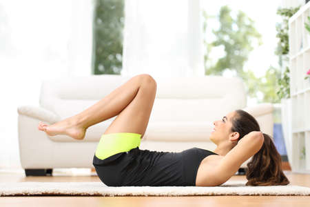 Photo pour Fitness girl doing crunches lying on the floor at home - image libre de droit
