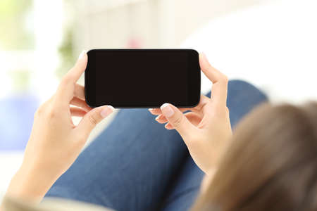 Photo for Back view of a close up of a woman hands watching media in a smart phone lying on a couch at home - Royalty Free Image