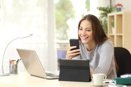 Photo pour Happy woman working using multiple devices on a desk at home - image libre de droit