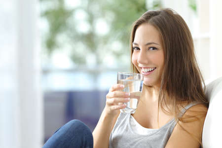 Photo pour Girl drinking water sitting on a couch at home and looking at camera - image libre de droit