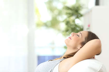 Foto de Profile of a beautiful woman relaxing lying on a couch at home - Imagen libre de derechos