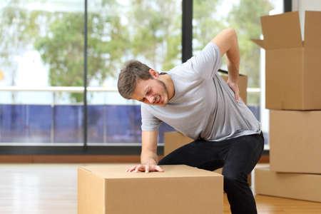 Photo pour Man suffering back ache moving boxes in his new house - image libre de droit