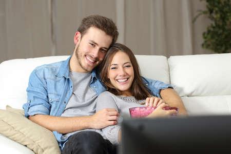 Foto de Happy couple watching a movie on tv sitting on a couch at home - Imagen libre de derechos