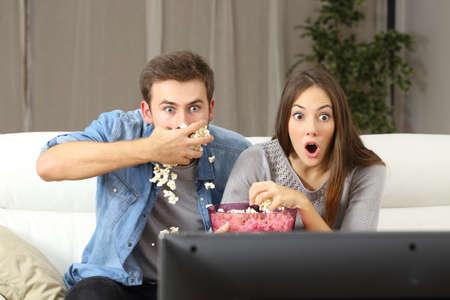 Foto de Amazed couple watching tv program sitting on a couch at home - Imagen libre de derechos