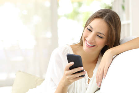 Photo pour Happy girl reading a message in a smart phone sitting on a couch at home - image libre de droit