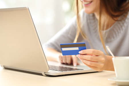 Photo pour Close up of a happy woman hand buying online with a laptop and paying with a credit card - image libre de droit