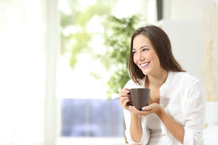 Foto de Pensive woman drinking coffee or tea and thinking looking sideways at home - Imagen libre de derechos