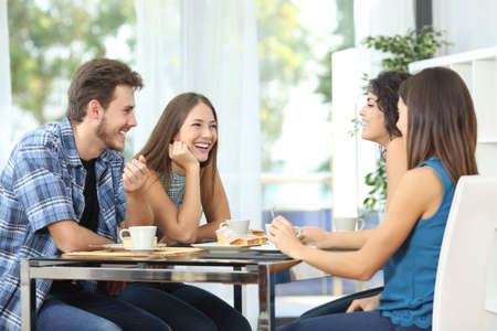 Photo for Group of 4 happy friends meeting and talking and eating desserts on a table at home - Royalty Free Image