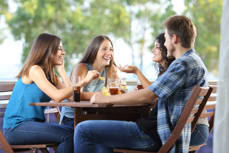 Photo for Group of four friends talking and drinking sitting in a terrace at home - Royalty Free Image