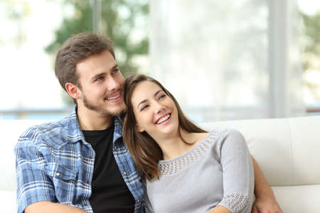 Photo for Happy couple thinking and looking sideways sitting on a couch at home - Royalty Free Image